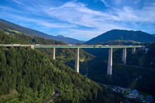 Aerial View Of A Road Bridge In The Alps Surrounded By Meadows, Forests And Mountains. Flying On Drone.
