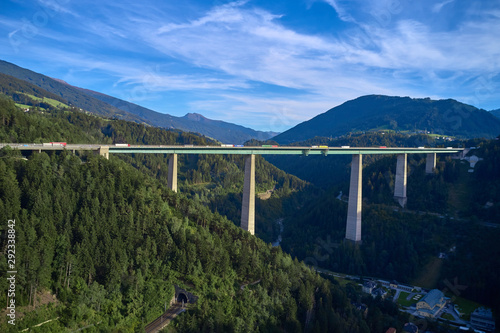 Fototapeta Aerial view of a road bridge in the Alps surrounded by meadows, forests and mountains