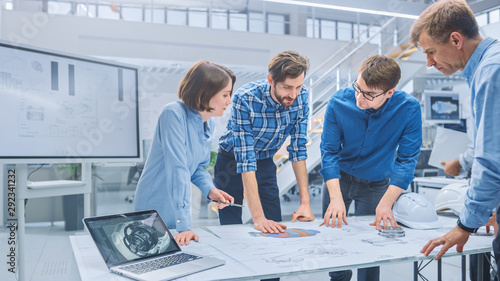 In the Industrial Engineering Facility: Diverse Group of Engineers and Technicians on a Meeting Gather Around Table with Engine Design Technical Drafts, Have Discussion, Analyse Technology