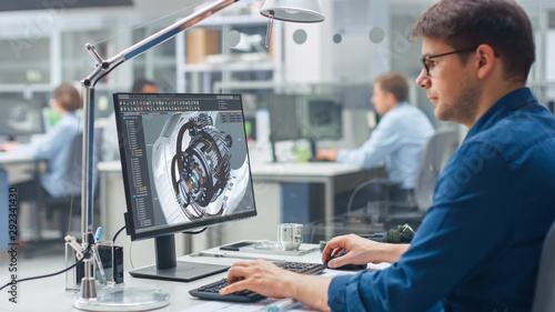 Fototapety, obrazy: Over the Shoulder Shot of Engineer Working with CAD Software on Desktop Computer, Screen Shows Technical Details and Drawings. In the Background Engineering Facility Specialising on Industrial Design