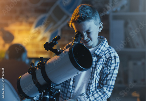 Cute boy watching stars through a telescope - 292342467