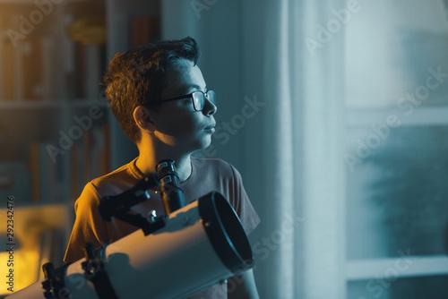 Photo Smart boy using a telescope and watching stars