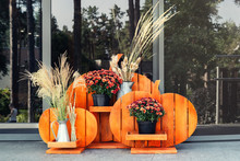 Orange Wooden Handmade Craft Halloween Style Flower-stand With Chrysanthemum And Dried Herb Flowers At House Porch. Autumn Holidays Home Decoration