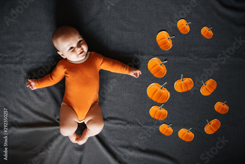 Fotomural  Newborn boy lies on dark background with pumpkins denoting six months