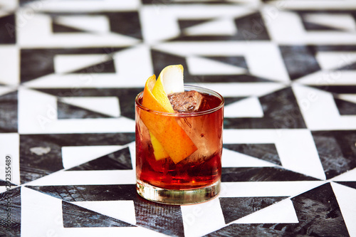 Tableau sur Toile Cocktail with orange peel in tumbler on black and white graphic patterned surfac