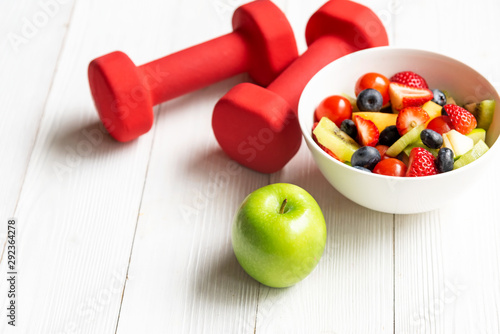 Healthy lifestyle for women diet with fresh fruits salad and dumbbells sport equipment, fruit healthy green apples on wooden. Healthy Concept.