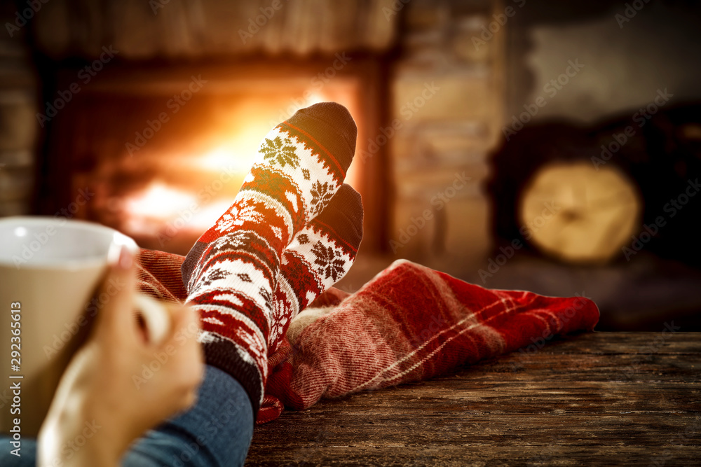 Fototapeta Woman legs with christmas wool socks and fireplace