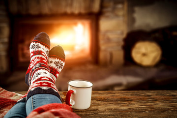 Woman legs with christmas wool socks and fireplace