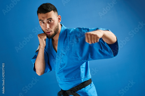 Asian Kazakh karate fighter in kimono uniform is combat on blue background with Canvas Print