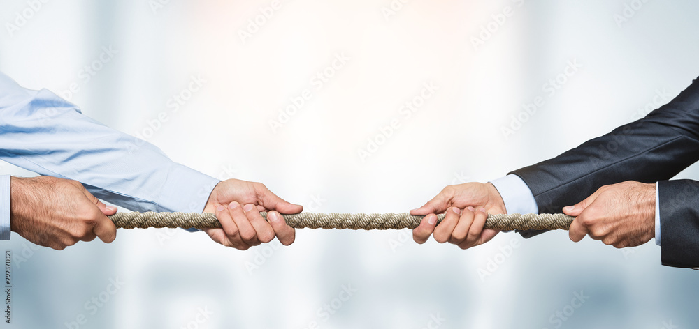 Fototapeta Tug of war, two businessman pulling a rope in opposite directions over defocused background with copy space
