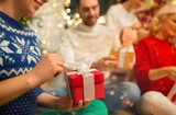 holidays, people and celebration and concept - close up of friends opening christmas gifts