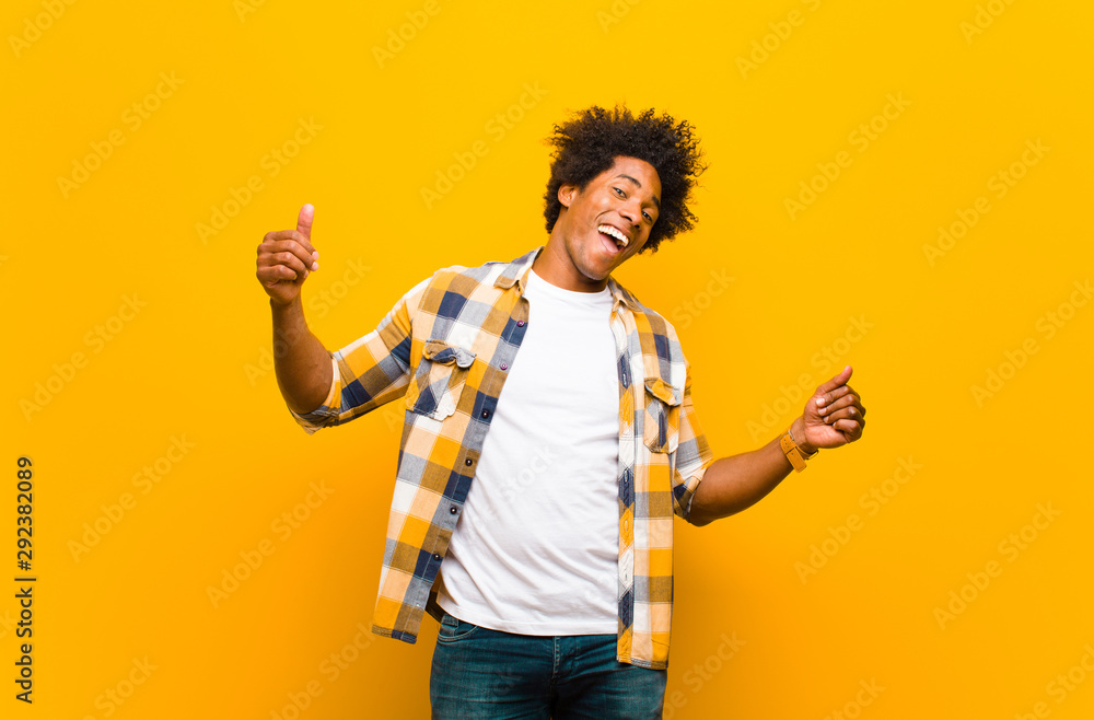 Fototapeta young black man smiling, feeling carefree, relaxed and happy, dancing and listening to music, having fun at a party against orange wall