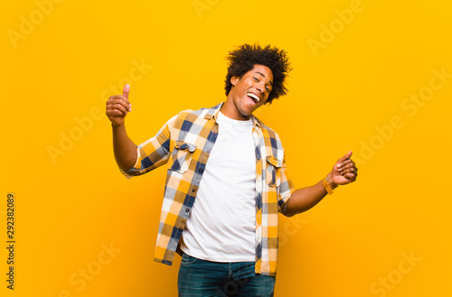 Photo Stands Dance School young black man smiling, feeling carefree, relaxed and happy, dancing and listening to music, having fun at a party against orange wall