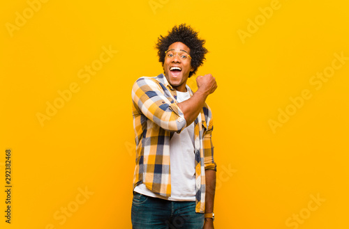 Pinturas sobre lienzo  young black man feeling happy, positive and successful, motivated when facing a