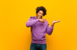 Leinwandbild Motiv young black man smiling cheerfully and pointing to copy space on palm on the side, showing or advertising an object against orange wall