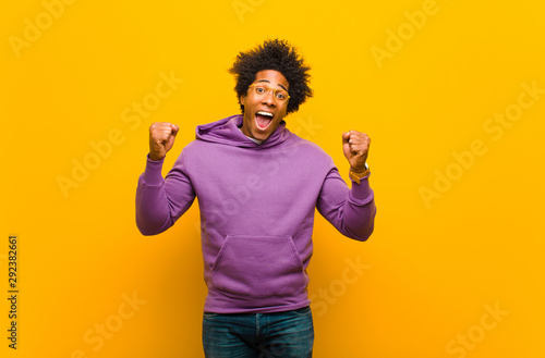 Cuadros en Lienzo  young black man feeling happy, positive and successful, celebrating victory, ach