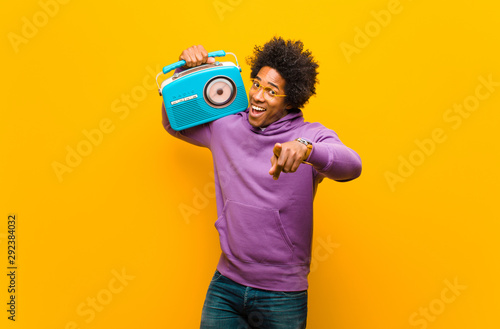 young african american man with a vintage radio against orange b - 292384032