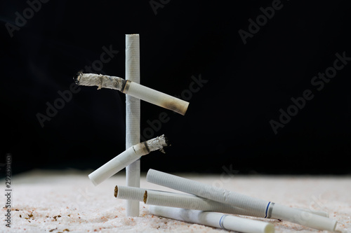 Fototapeta Cigarette butts white stacked in the form of a tombstone cross