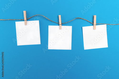 Cuadros en Lienzo  Three empty little sheets of paper hold by wooden clothespins on a string