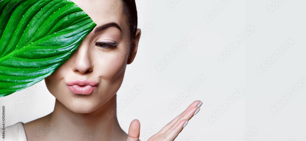 Fototapeta Portrait of young beautiful woman with healthy glow perfect smooth skin holds green tropical leaf. Model with natural nude make up. Gray background.