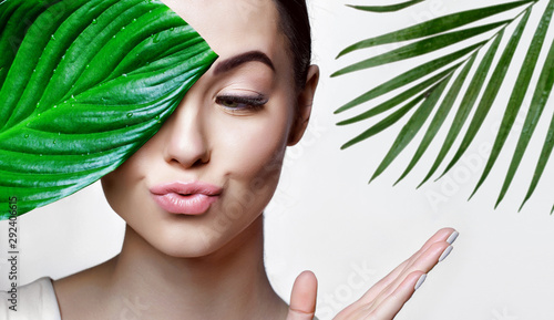 Valokuva  Portrait of young beautiful woman with healthy glow perfect smooth skin holds green tropical leaf
