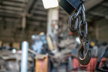 Powerful Crane Hook Close Up. Against The Background Of An Industrial Plant. Industrial Background.