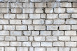 Vintage and dirty white brick wall background texture with smudges and cracks