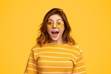 Amused Woman In Bright Clothes And Sunglasses Looking At Camera