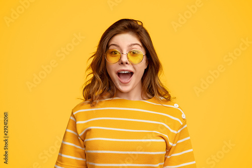 Vászonkép Amused woman in bright clothes and sunglasses looking at camera