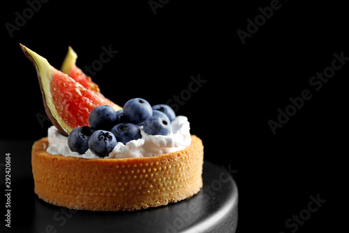 Fotografie, Obraz Tart with blueberries and figs on black table against dark background, space for text