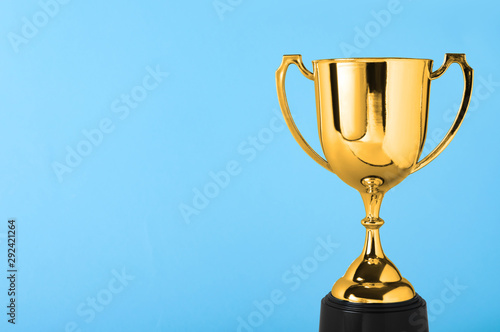 Fotomural  Golden trophy cup on blue background. Space for text