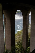 Vertical Shot Where Stone Arcs Cover A View Of The River Where A Waterfall Falls