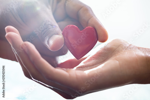 Male Hand Giving Heart To Female Fototapete