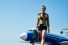 Stewardess. Journey And Jet Trip. Woman And Commercial Plane. Portrait Of Charming Stewardess Wearing In Blue Uniform. Stewardess And Travel Time. Business People And Commercial Jetliner.