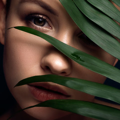 Obraz na Szkle Do Spa Brunette european woman on a neutral dark background with leaves on her face. She have flawless fresh clean skin. Eco spa concept