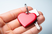 Human Hand Holding Red Heart Shape Key Chain With Key