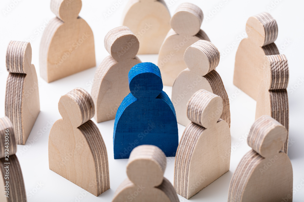 Fototapety, obrazy: Wooden Figures Around Blue Human Figure Over Desk