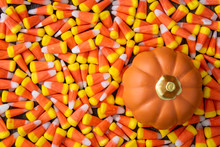 Background Of Yellow, Orange, And White Candy Corn For The Holidays, With An Orange Ceramic Pumpkin