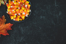Bowl Of Autumn Fall Halloween Candy Corn Spilled On Black Slate With Fall Autumn Leaves Decor Decoration With Copy Space