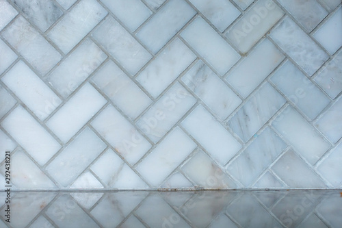 white and gray herringbone italian marble tile in a kitchen as a backsplash with Fototapeta