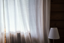 Transparent Curtains On The Window Through Which Sunlight Passes And The Shadow From The Jalousie Is Visible, A Lamp Stands Next To It, Against The Background Of A Wooden Wall.