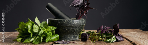 panoramic shot of mortar and pestle with basil on wooden table isolated on black Wallpaper Mural