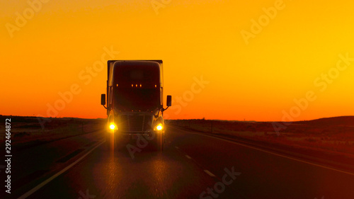 Cuadros en Lienzo  CLOSE UP LENS FLARE: Semi truck driving directly into camera at golden sunset