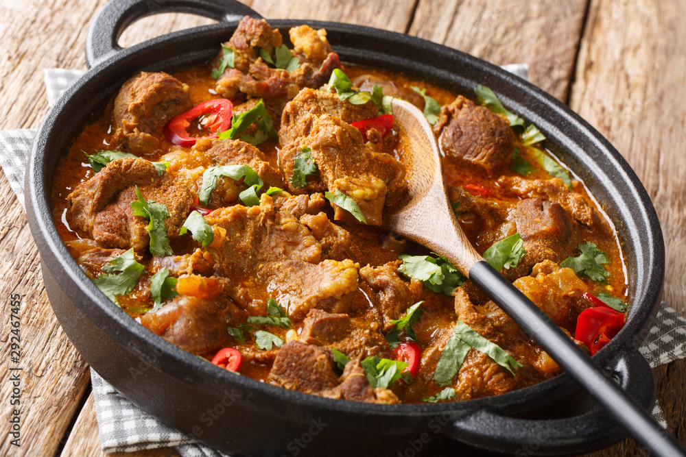 Fototapeta Boneless Lamb slow cooked with yogurt and traditional Indian warm spices close-up in a pan. horizontal