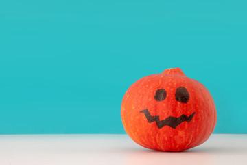 Halloween holiday creative background with jack o lantern pumpkin on blue background
