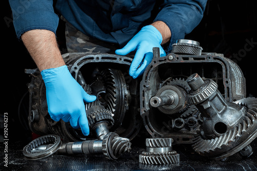 Valokuvatapetti Hands of a male repairman in blue gloves on a background of a gearbox, close-up