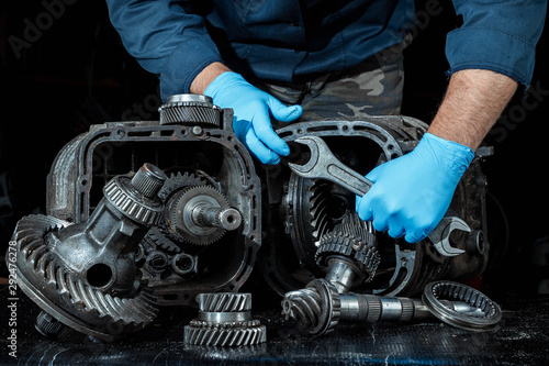 Fényképezés  Hands of a male repairman in blue gloves on a background of a gearbox, close-up