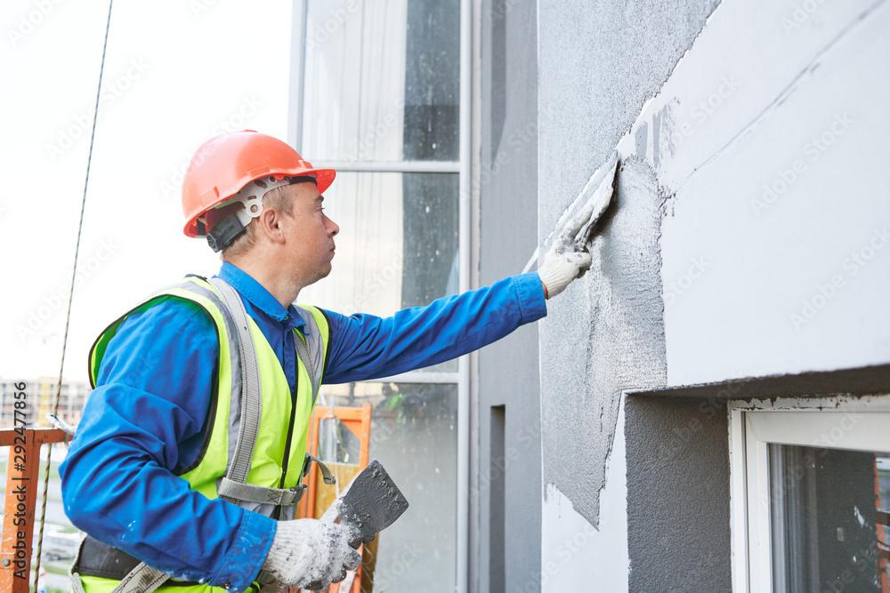 Fototapeta Facade worker plastering external wall of building
