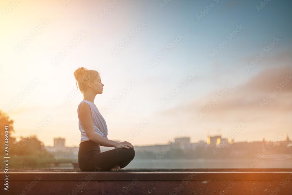 Fototapeta Girl practice yoga early morning on pier