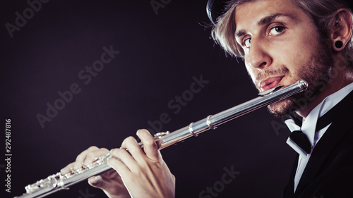 Elegantly dressed male musician playing flute Fototapete